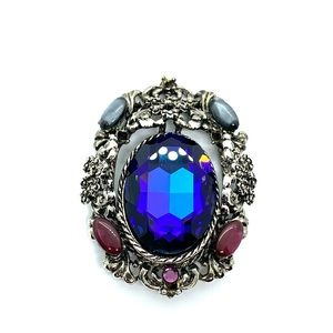 Accessory brooch with blue faux crystal.